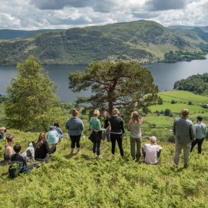 A group of people on a fell side looking down toward a lake.