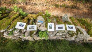 some photographs laid out in top of a dry stone wall.