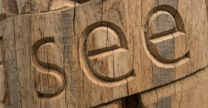the word 'see' carved into wood.