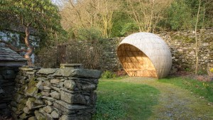 a circular wooden structure in a cottage garden.