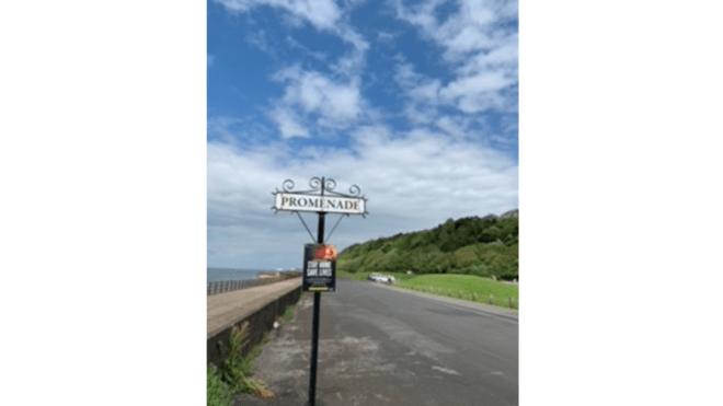 A promenade sign next to a road at Maryport.