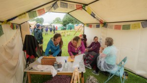 Tent with bunting and a group of people, writing at a table at Eskfest