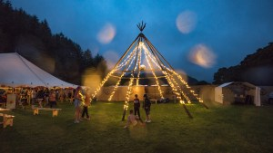 Eskfest at night, a tepee structure with no fabric and fairy lights strung around