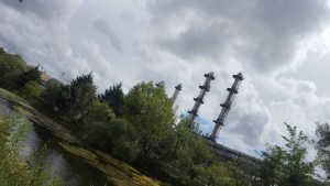 Riverbank with trees, some metal, industrial towers and sky with clouds.