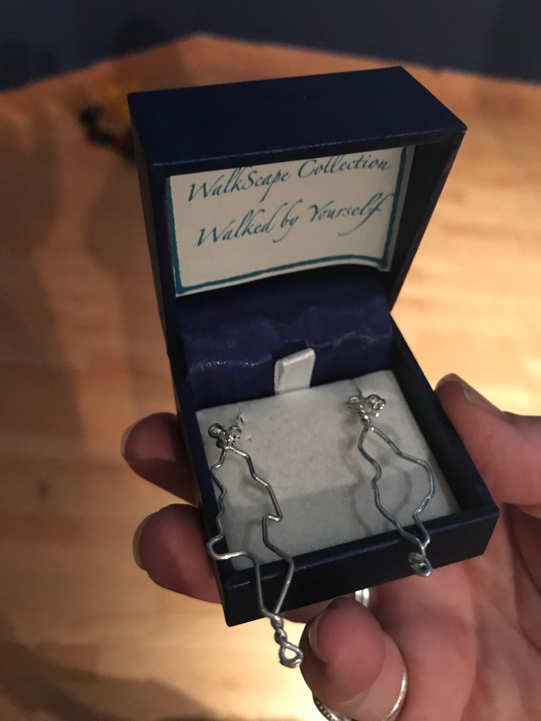 Two silver earrings made in the shape of tracks of walks, held in a box.