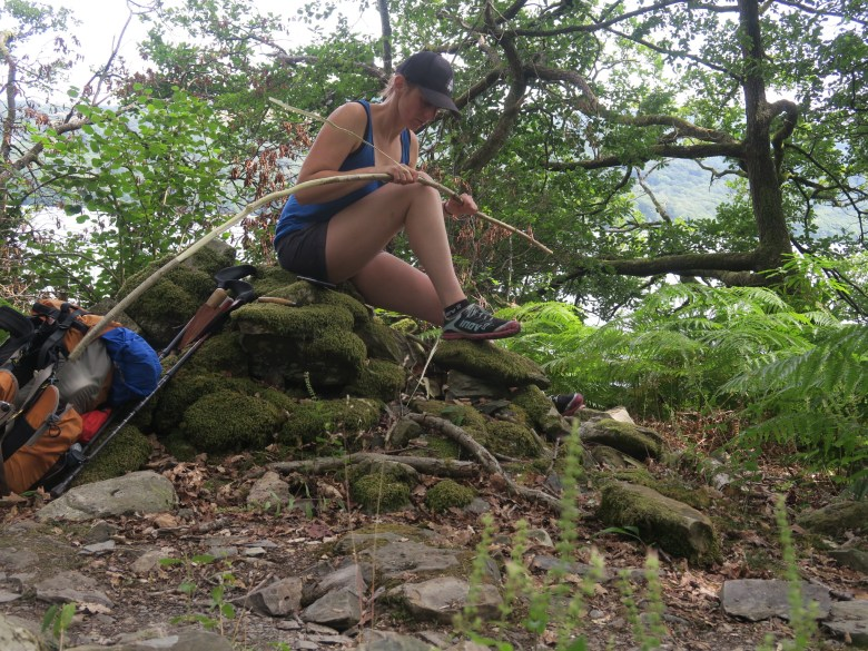 Lorna Singleton pictured sitting on a mossy stone, bending hazel sticks, ready for weaving. Lorna is dressed in dark shorts and a blue vest, and has a bag resting on the ground to her left. There is bracken growing, trees behind her, and the lake is visible beyond.