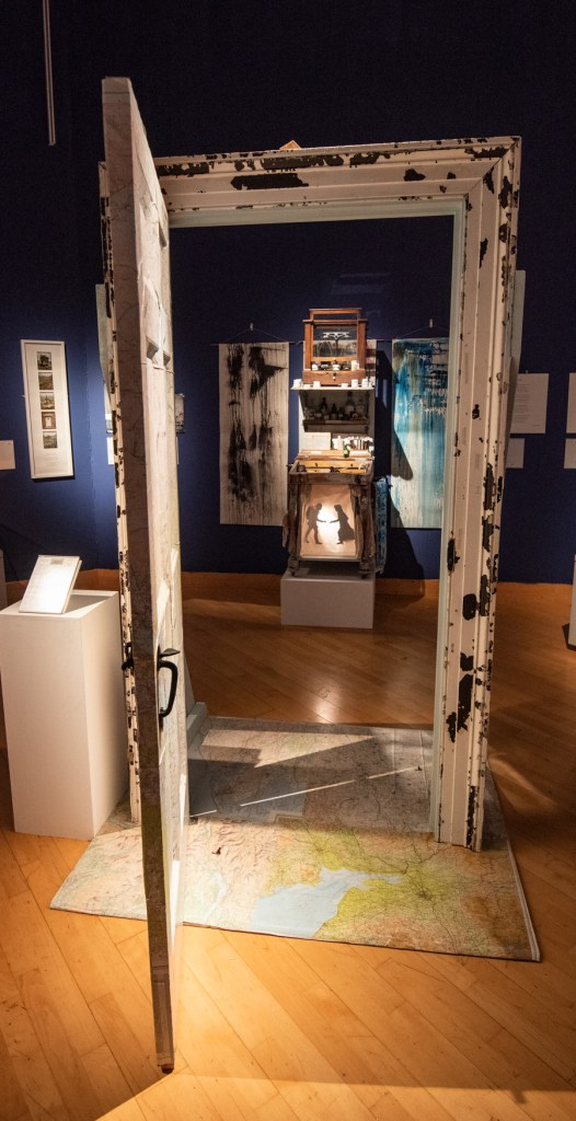 A doorway placed into a gallery. The doorway is propped open and stands on a plinth that is covered in maps. through the doorway a cabinet is visible, and there are paintings on the wall.