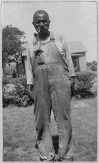 Image of an enslaved man, shown wearing dungarees and smoking a pipe. He is standing on grass, with a building visible behind him.