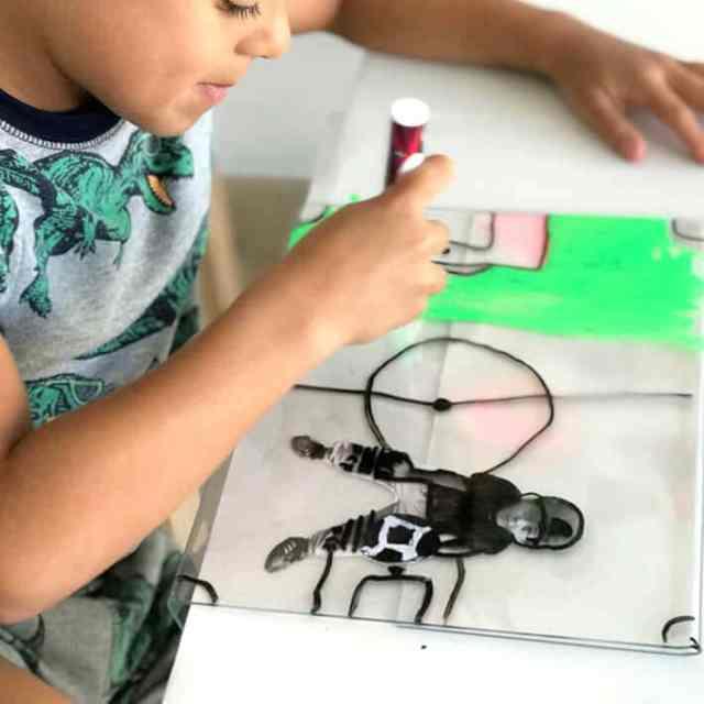 Boy drawing creating mixed media artwork on plexiglass