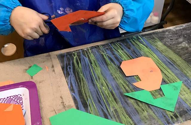 Boy cutting shapes for mixed media cities – Paul Klee Art for Kids