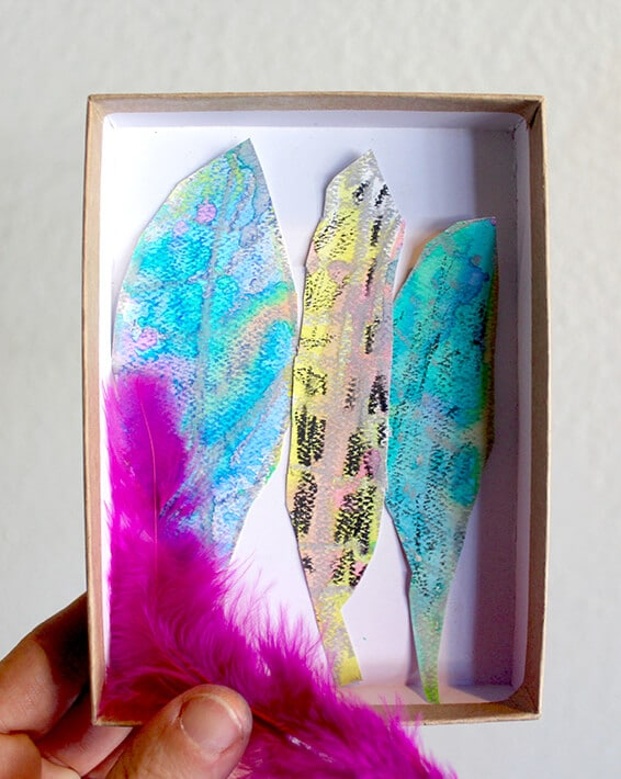 Nature drawing – hand holding pink feathers & box with cut out painted feathers in it
