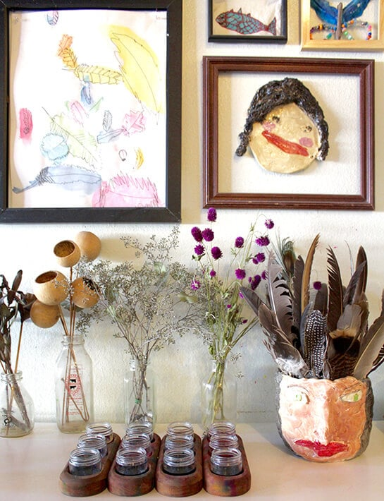 Easy nature drawing ideas for kids – artwork hanging in frames on the wall along with flowers & feather for observational drawing
