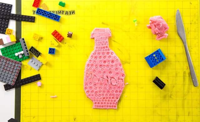 LEGO prints made in playdough – playdough potion bottle with LEGOS and butter knife on mat