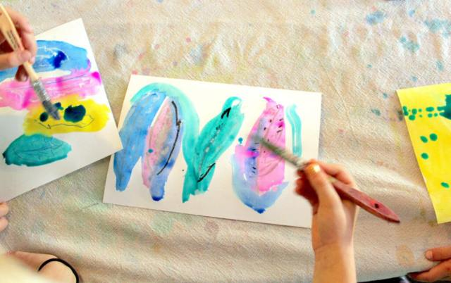 Student painting feathers with a brush in this easy nature art project