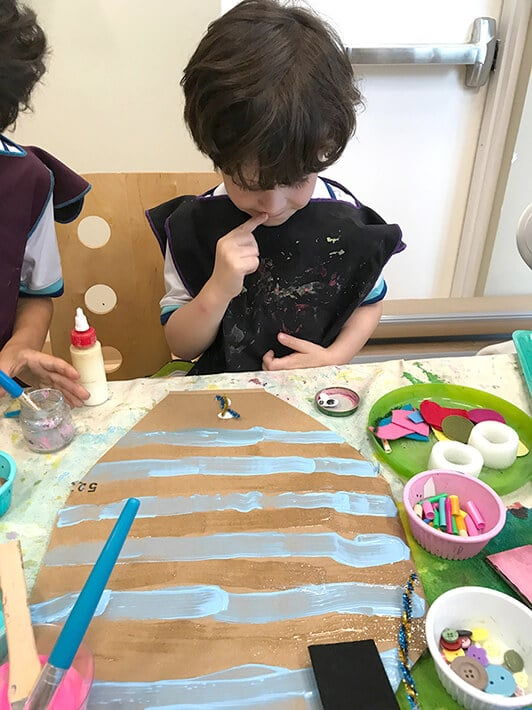 Boy creating animal mask for kids with blue stripes on cardboard