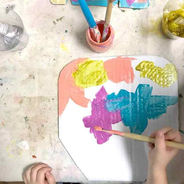 Child painting cardboard shape for Miró inspired animal mask for kids