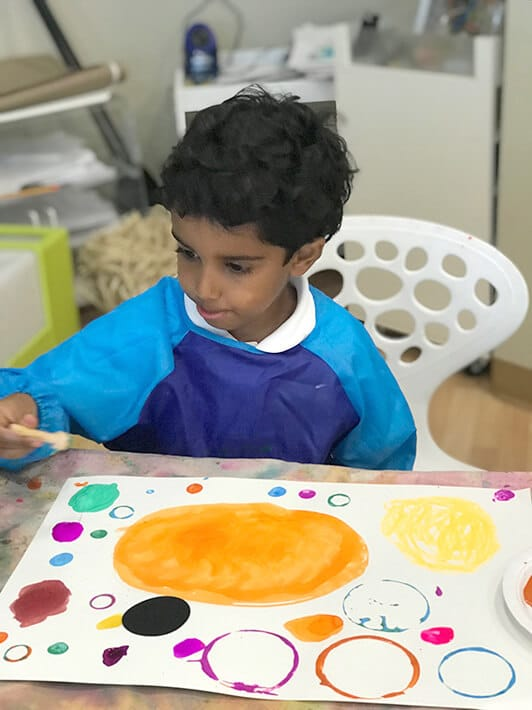 Boy painting Yayoi Kusama Inspired Dot Paintings for Kids