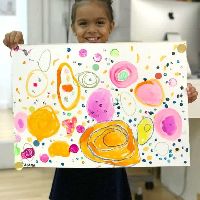 Child holding up colorful Yayoi Kusama Inspired Dot Painting