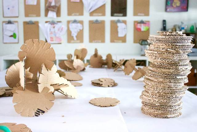 Stack of cardboard building discs along with an assembled cardboard sculpture