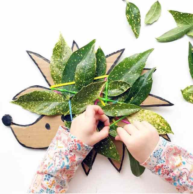 Cardboard cut out hedgehog with leaves attached for fine motor nature weaving for kids.