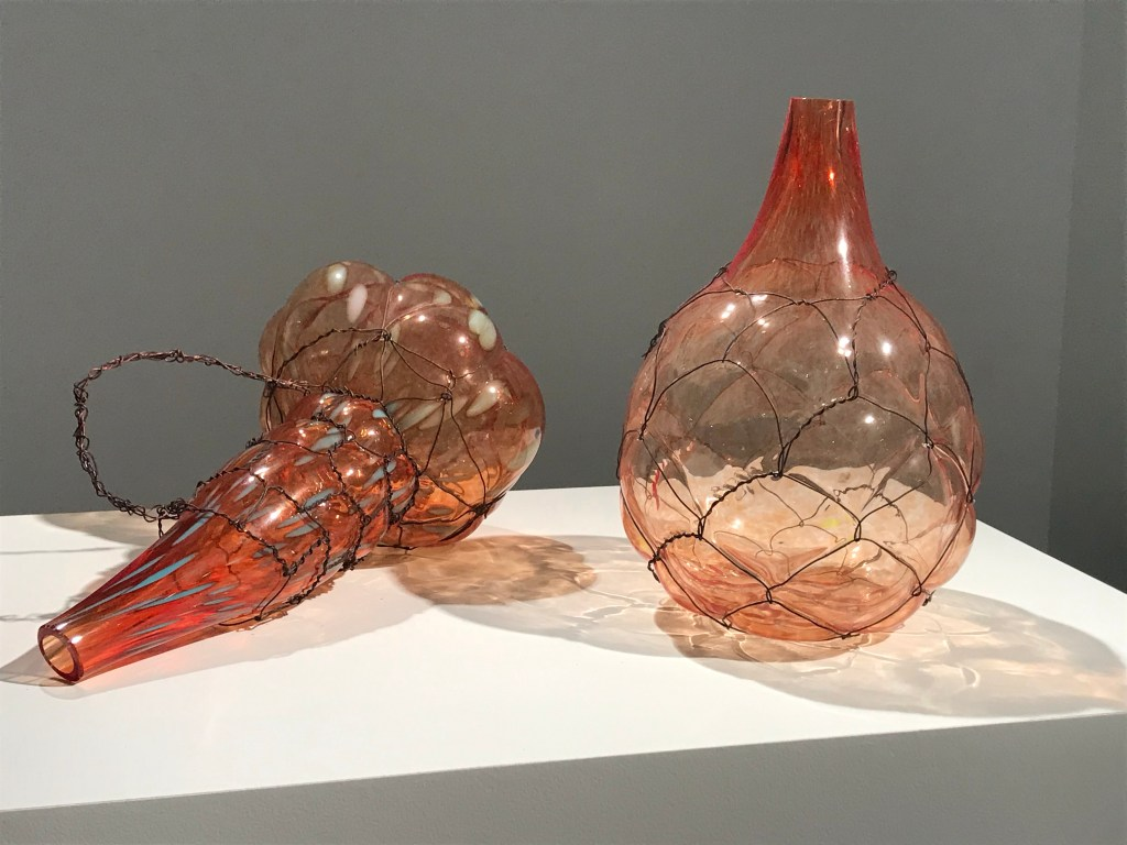 "Two red Glas Objekts blown into a Metal Cage"" by Gala Fernández"