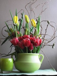 Tulips and curly willow arranged in a ceramic urn.