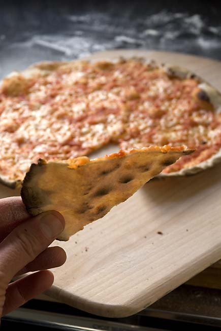 Cracker-crust pizza is so thin the light shines through it
