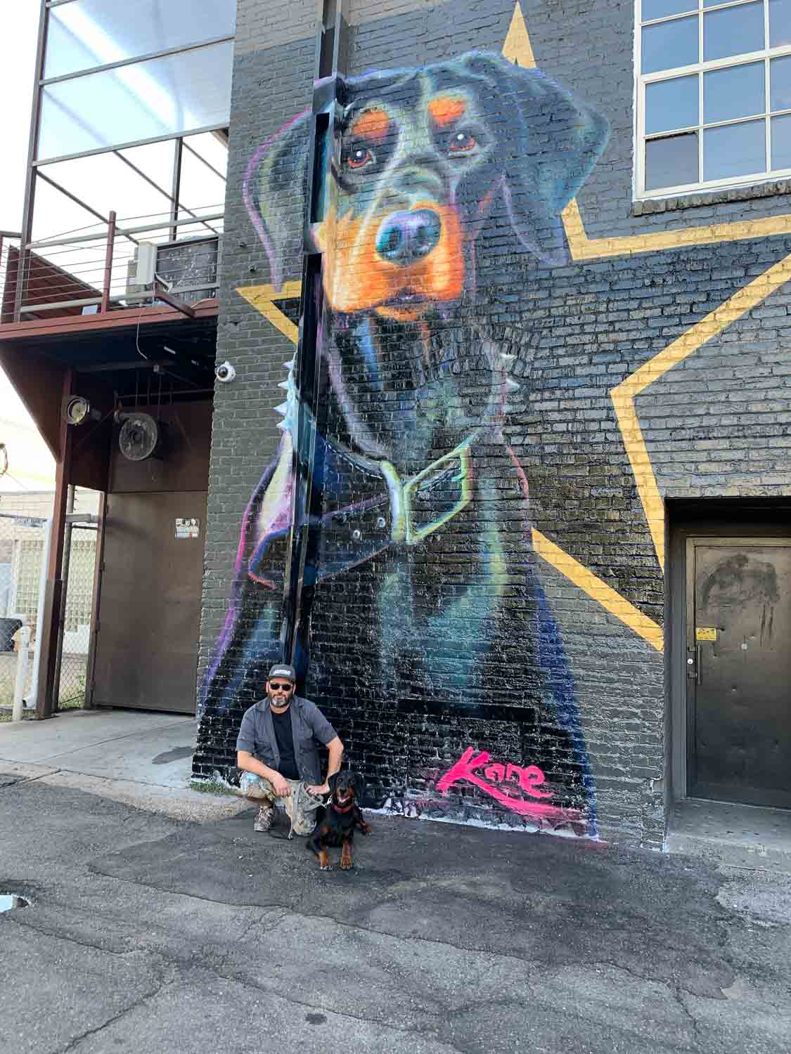 "My dobie girl ""Kita"" immortalized in the alley at 11th and Broadway. My beautiful muse pictured here with me. Oils on brick 20' x 12'. —Patrick Kane McGregor"