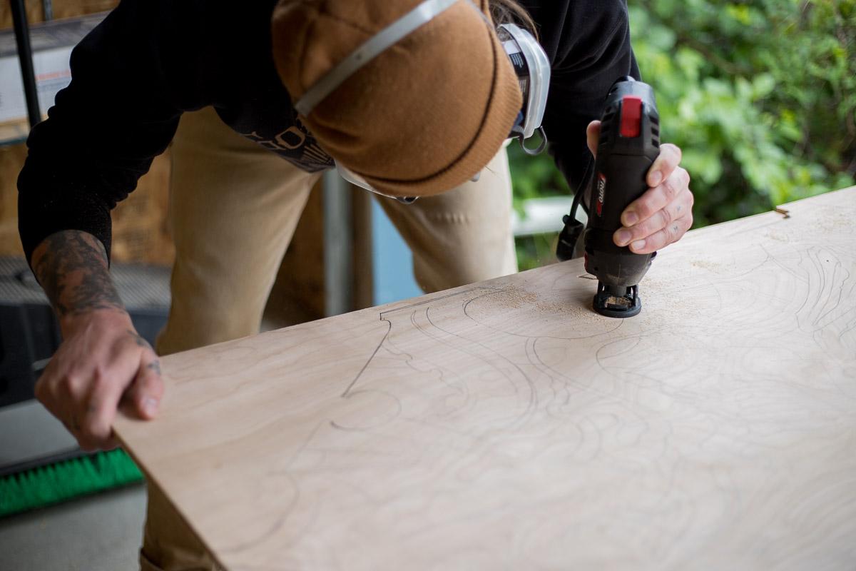 Artist Scott Santee working on his wood cutouts, Golden, Colorado
