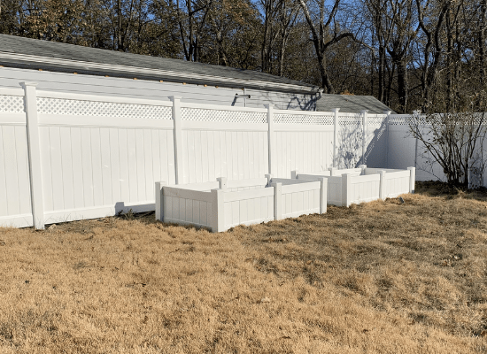 White vinyl privacy fence with lattice top and two raised pvc garden beds