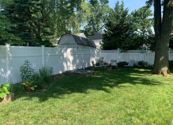 Tall white vinyl privacy fence on the left that meets with open topped vinyl privacy fence in the back