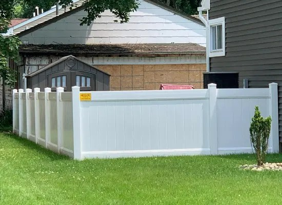 White vinyl fence with Deco Rail installed by Artistic Fence enclosing a homeowners backyard in New Jersey