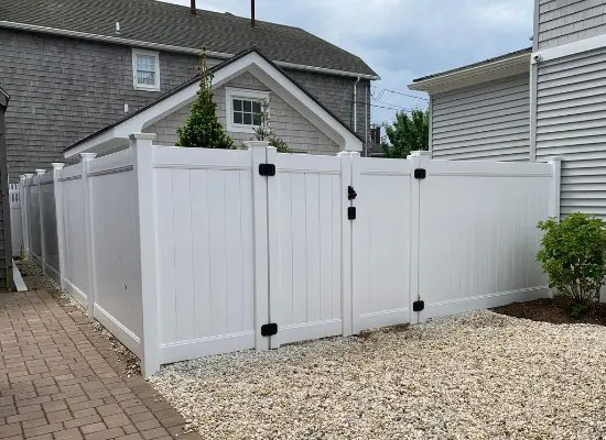 White vinyl privacy fence with Deco Rail and a double gate enclosing a homeowner's backyard and garage