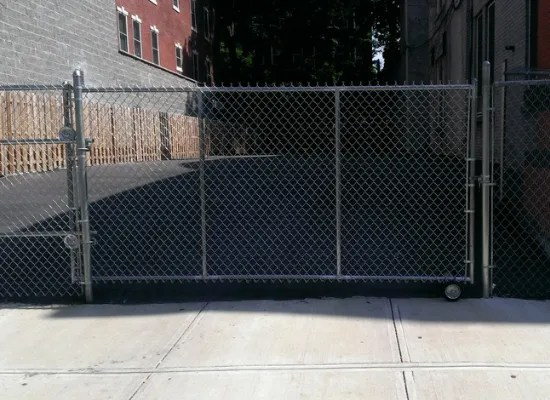 Silver chain link fence and rolling driveway gate