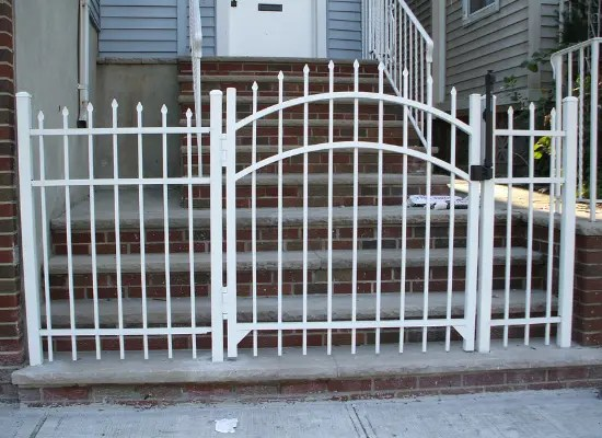 White aluminum fence and single arch gate with finials