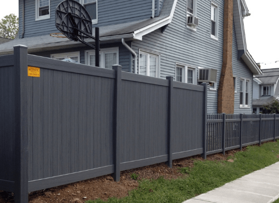 Dark grey vinyl privacy fence and straight top picket fence