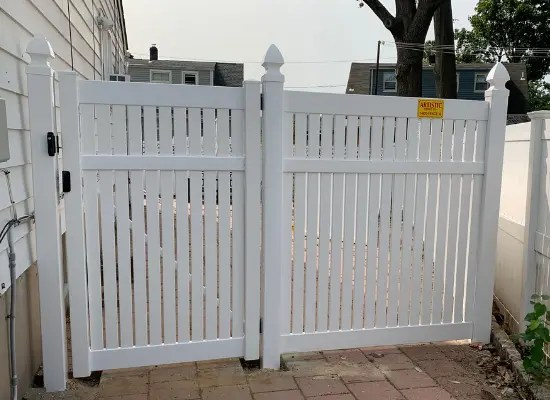 Keywest style vinyl semi privacy fence with a tall gate installed by Artistic Fence Company