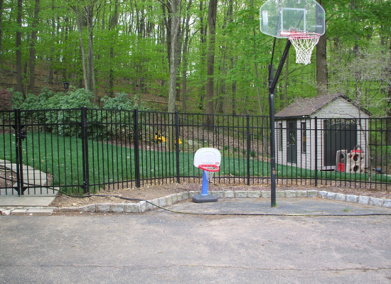 Black aluminum fence separating a residential backyard and driveway with two basketball hoops