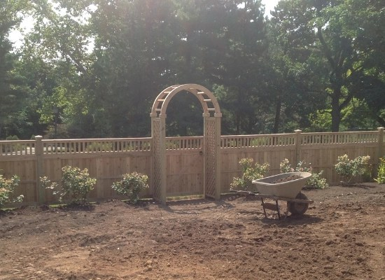 Wood rounded arbor with gate and closed top privacy fence