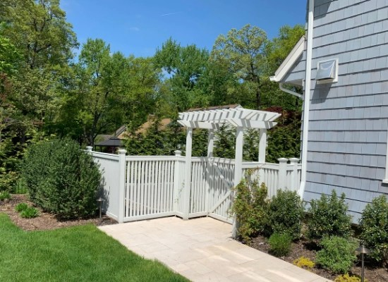 White picket fence and vinyl arbor with flat top