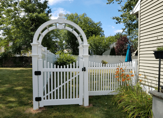 White vinyl picket fence, gate, and arbor installed by Artistic Fence Company of northern NJ