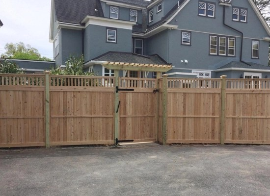 Wood closed top privacy fence with tall gate and flat arbor
