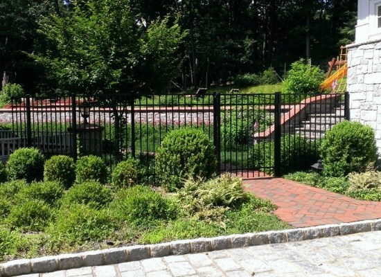 Black aluminum fence in a yard with single flat top gate