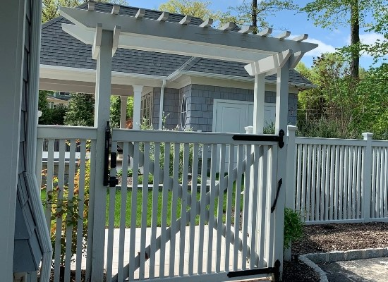 White picket vinyl gate with black hardware and a white arbor