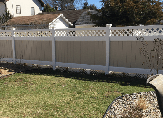 Tan and white vinyl privacy fence with lattice top