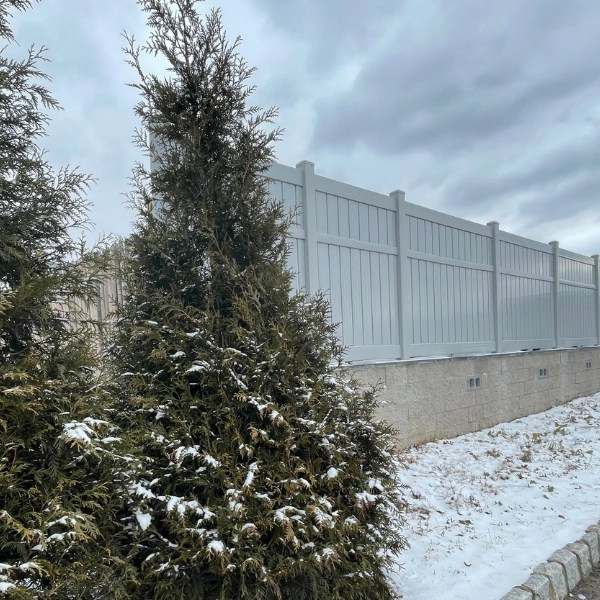 Semi privacy vinyl fence on top of a retaining wall with snow on the ground in the winter