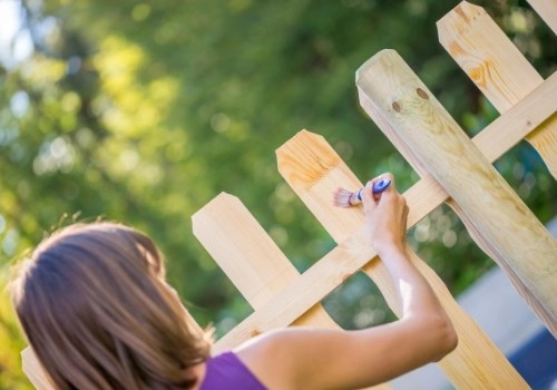 A woman staining her own wood picket fence