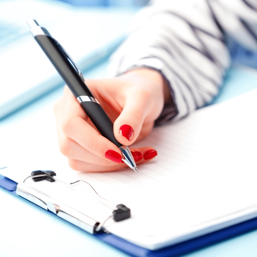 Woman's hand with red nail polish holding a pen and signing a ST-8 form on a clipboard