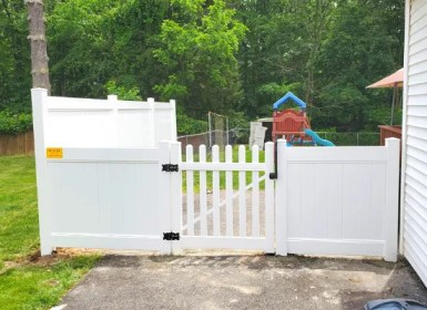 White PVC fence installed by Artistic Fence | 4ft and 6ft solid suburban pvc fence with deco-rail and a bar harbor walk gate