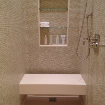 Her bathroom shower in penny tile with limestone slab floor and bench